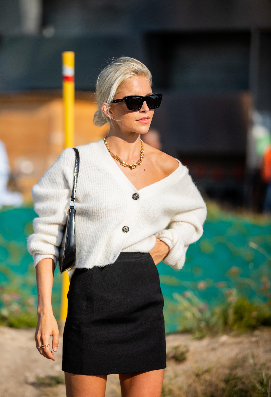 Caroline Daur con cardigan y minifalda negra.