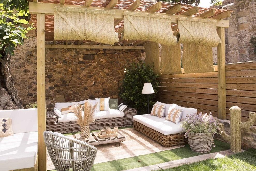En el porche, pérgola de La Pèrgola, estores de Moble Bamboo, sofás de  Maisons du Monde,cesto de ratán de Bossvi, sillón de ratán de Merc&Cia, alfombra de Calma House,  Cáctus de Muy Mucho, lámpara de pie de Faro y almohadones de Sira y Catalina House.