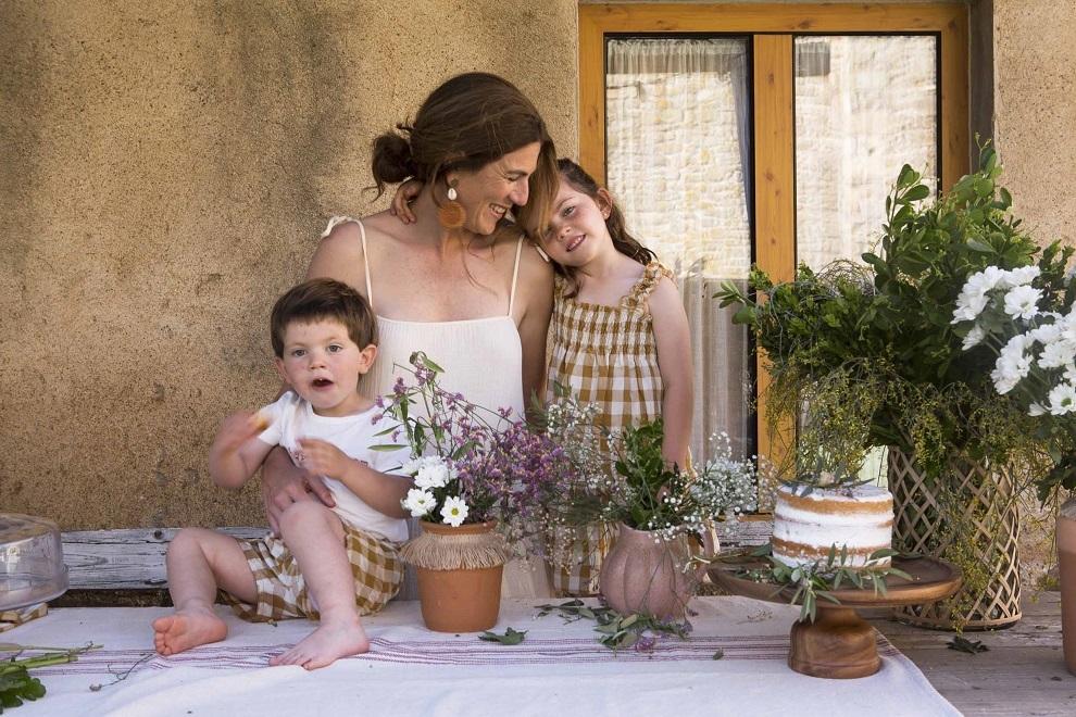 Pía, de Zara Home y pendientes de Campmany,  con sus dos hijos, de Búho,  en un rincón del porche. Tiesto de Muy Mucho y  bandeja de Catalina House.