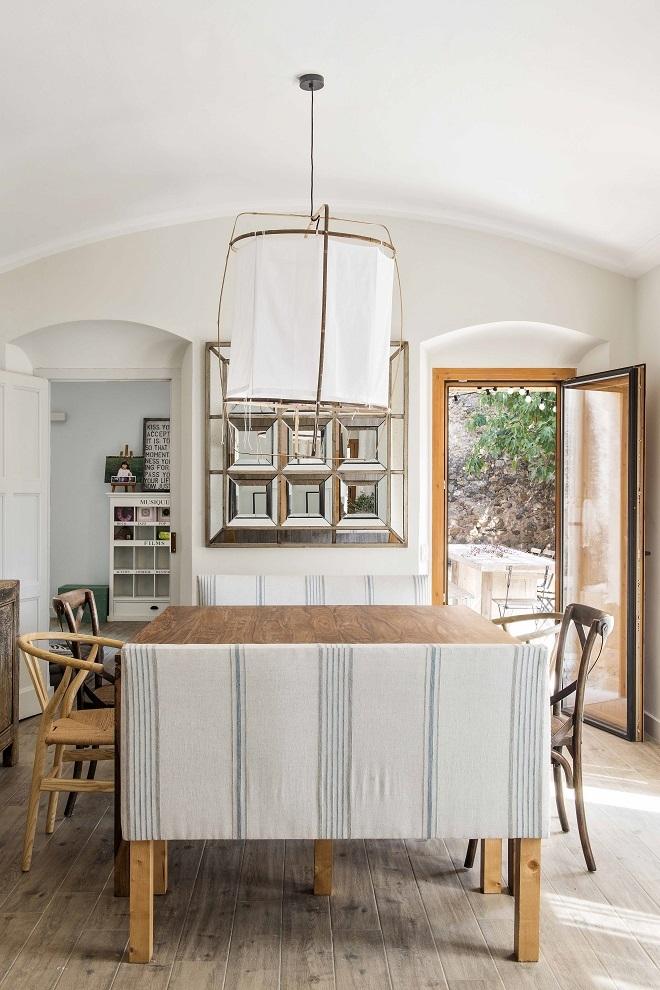 En el comedor, banco tapizado con tela de Güell Lamadrid, mesa de Maisons du Monde, sillas de Domestico, lámpara de techo de Ayiluminate y espejo de Fandy Home.