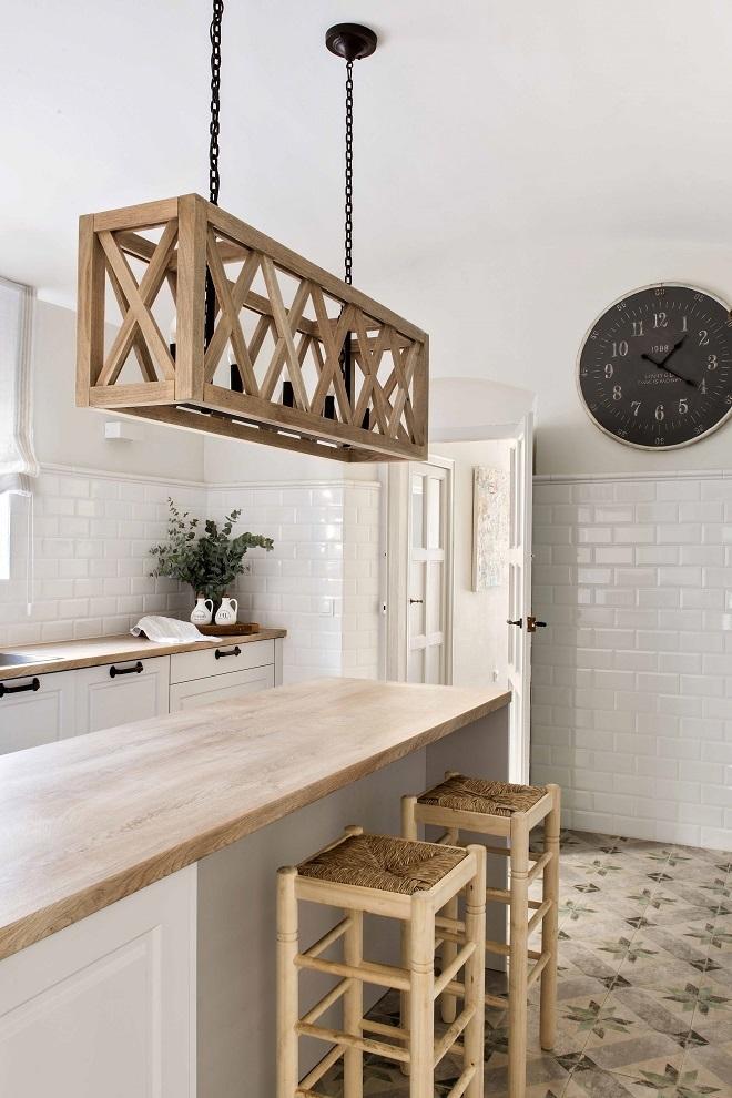 En la cocina, reloj de pared de Maisons du Monde, muebles de Meine Kuchen, taburetes de Bambú Bambú en La Bisbal y lámpara de techo de Fancy Home.