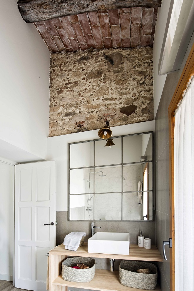 En el cuarto de baño, espejo y aplique de Pomax, muebles a medida realizados con madera de pino y cestas de Zara Home.