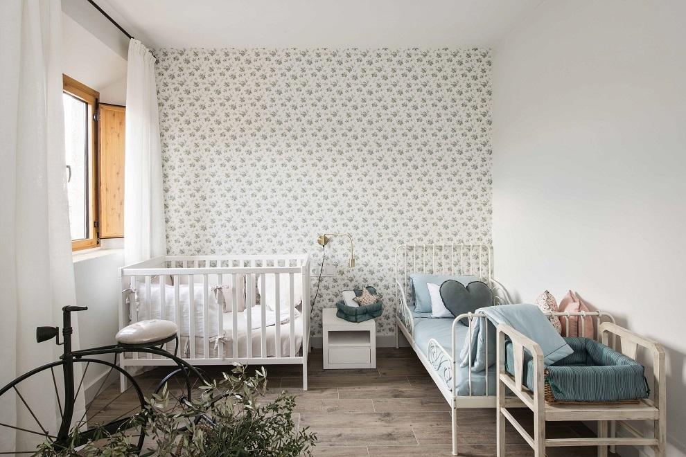 El cuarto de dormir de los niños, con cama y cuna de Ikea, papel pintado de Sandberg, aplique y mesilla  de Maisons du Monde y bicicleta decorativa de Ixia.