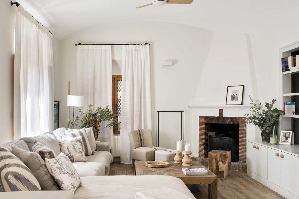 En el salón, sofá y mesa de centro de Maisons du Monde, Butaca,reposapies y porta velas de Pomax, bandeja del centro Ixia, cortinas de tela de yute y almohadones de Güell Lamadrid.