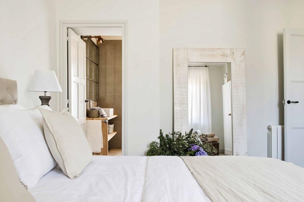 El dormitorio principal, en tonos claros con espejo apoyado en el suelo.