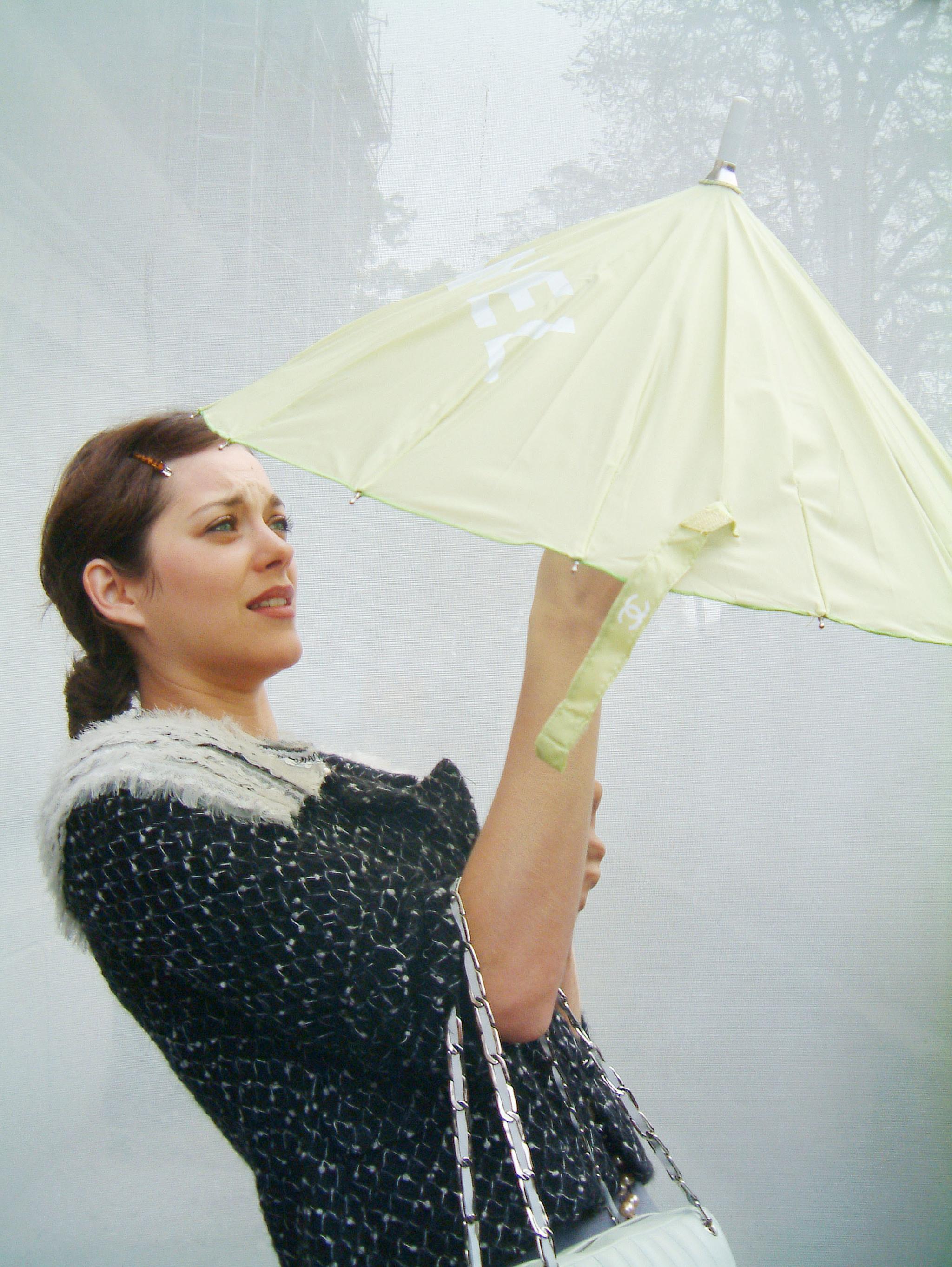 Tratando de cerrar su paraguas a la entrada del desfile de Chanel en 2005