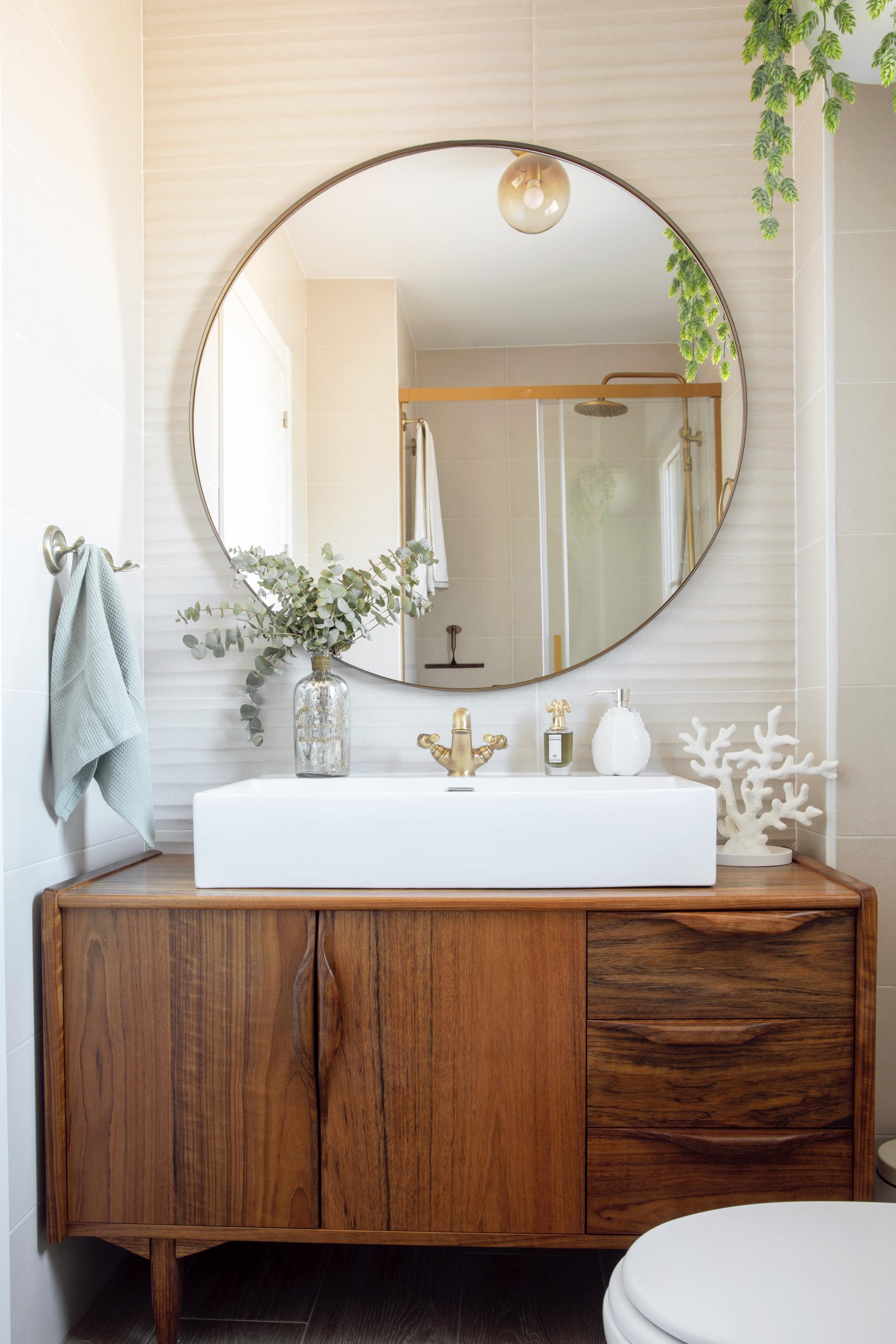 El baño principal con mueble hecho a medida en madera de mongoy por Lakari Kala y espejo ovalado.