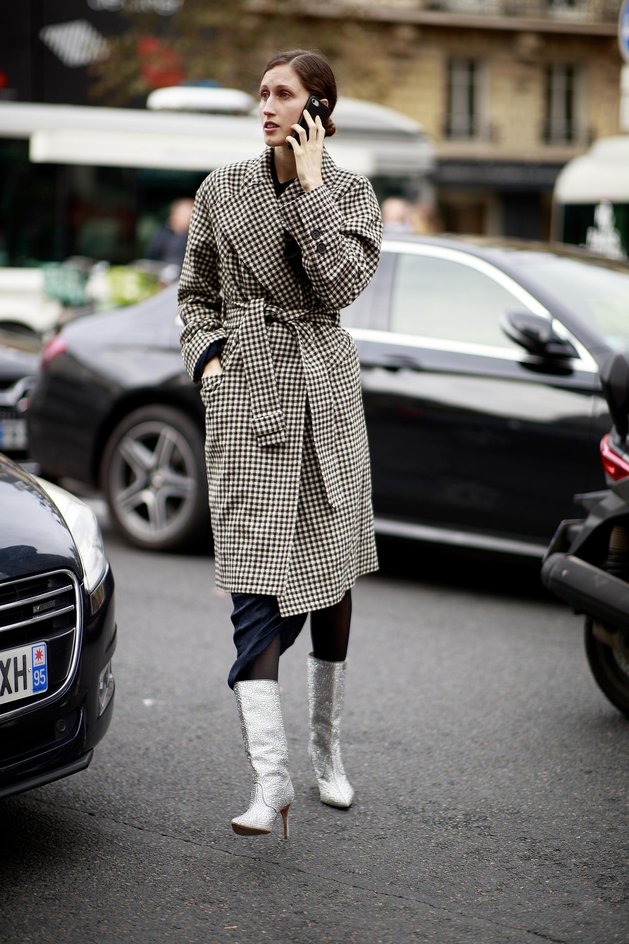 Anna Cleveland con gabardina de cuadros con botas plata.