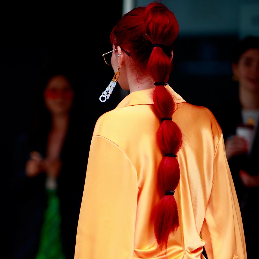 En el street style de la London Fashion Week hemos visto coletas altas con burbujas a las insiders en tonos de pelo tan llamativos como este pelirrojo.