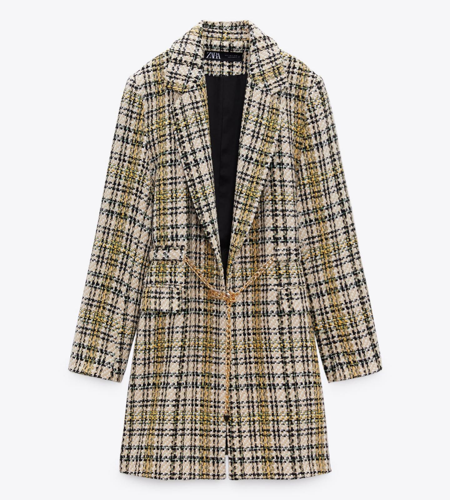Uno más económico: abrigo estructura con cinduron dorado de cuello solapa y manga larga. Zara (69,95 euros).