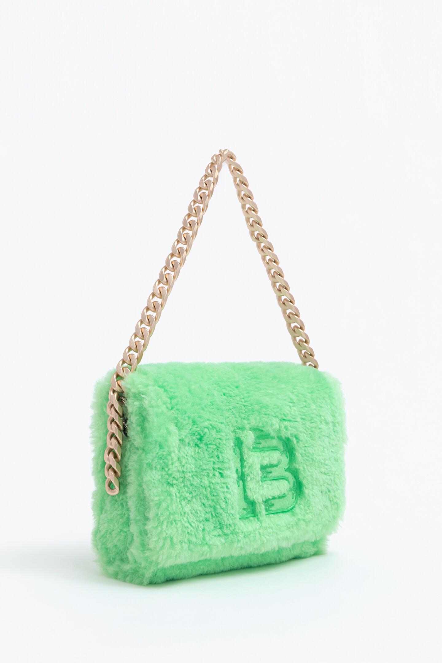 El bolso de pelo en color verde menta de Bimba y Lola nos encanta con vaquero y camisa blanca y trench camel. Bimba y Lola (195 euros).