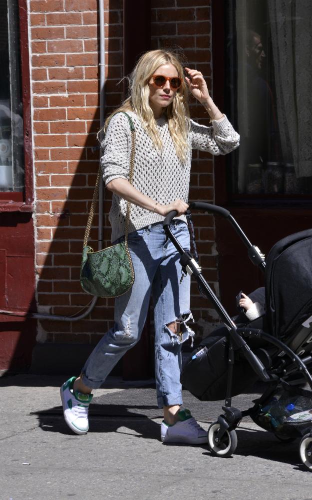 Sienna Miller con boyfriend jeans, sneakers, jersey calado de algodón y snake print bag