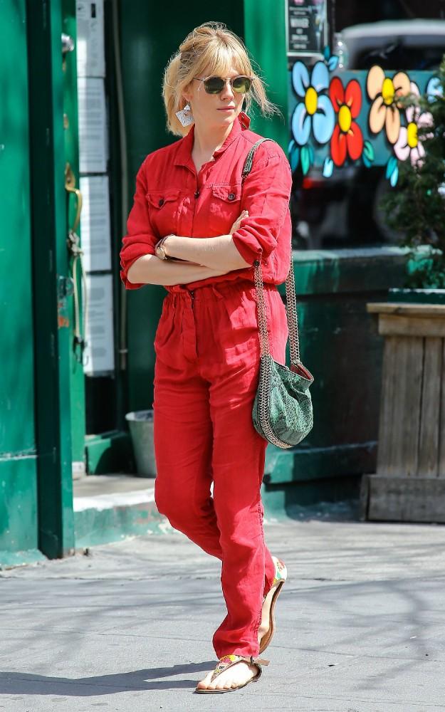 Sienna Miller con carpenter jumpsuit, sandalias planas de inspiración tribal y snake print bag