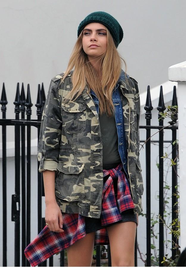Cara Delevingne con chaqueta de camuflaje, minifalda, camisa de cuadros, cazadora denim, botas.