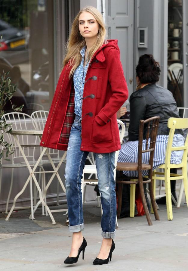 Cara Delevingne con ripped boyfriend jeans, trenca roja y salones negros.
