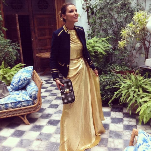 Look vestido dorado de Dior con chaqueta militar