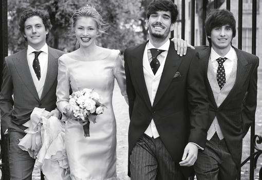 Novio con caqué, testigos con traje y chaqué y novia con vestido de volantes.