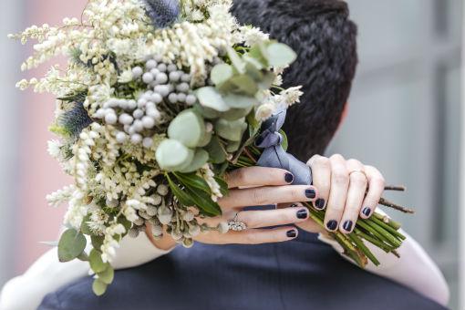 Una novia con su ramo nupcial en la mano