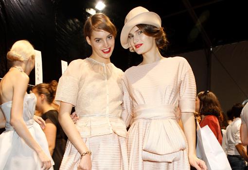 Dos modelos de pasarela en el backstage vestidas de invitadas en tonos nude.