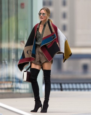 Olivia Palermo se atreve con lo improbable: poncho + gafas espejo + botas ajustadísimas