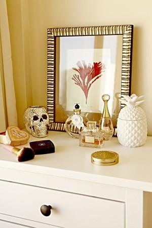 Sobre su tocador, adornos tropicales de cerámica, gadgets de estilo kitsch y sus perfumes preferidos, Valentina o Miss Dior.
