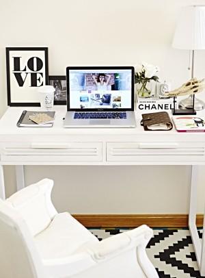 En blanco y negro, su mesa de trabajo con flores frescas, cuadros XS con mensajes optimistas y velas aromáticas de Diptyque.