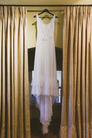 Vestido de novia colgado de unas cortinas.