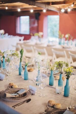 Montaje de una mesa de boda con botellitas azules de decoración