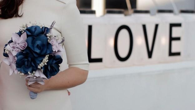 Una novia sosteniendo un ramo de flores de papel.