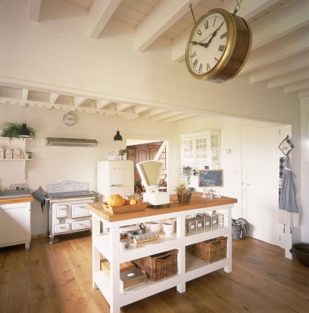 Una cocina con un reloj colgado en medio.