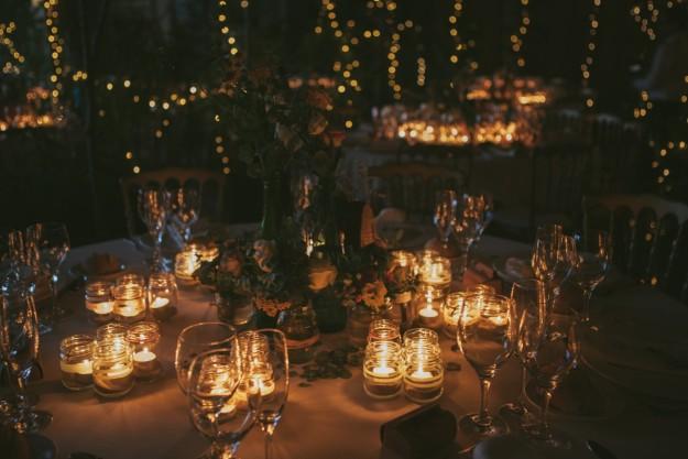 Una mesa nupcial ilumninada con velas.