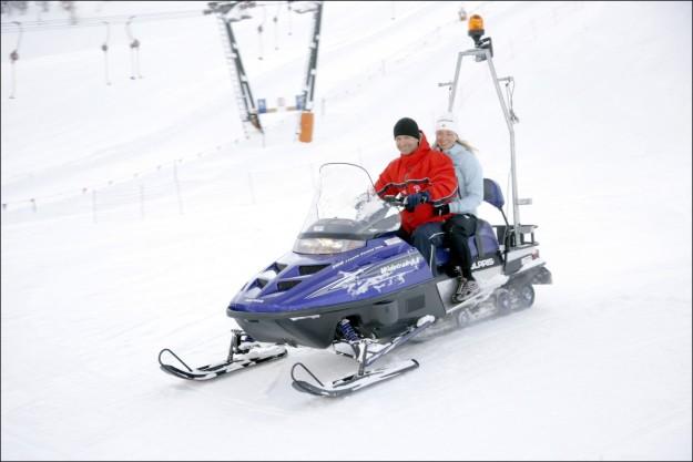 Una pareja montada en una moto de nieve.