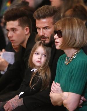 David Beckham con dos de sus hijos, Brooklyn, el mayor, y Harper, la pequeña, que observa a la editora de moda Anna Wintour.