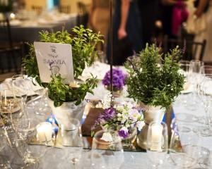 Aparecen una serie de flores verdes y moradas en una mesa.