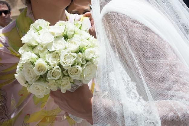 Aparece el ramo en primer plano sujeto por la novia.