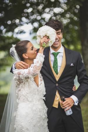 María y Roberto riendo mientras la novia le hace una pequeña broma con el ramo. Ambos aparecen felices y sonrientes.
