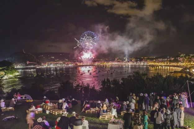 Aparecen todos los invitados sentados en palets con cojines mientras veían sorprendidos los fuegos artificiales.