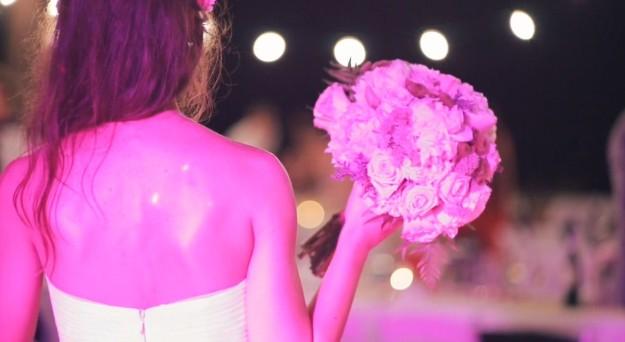 Una novia de espaldas con un ramo de flores.