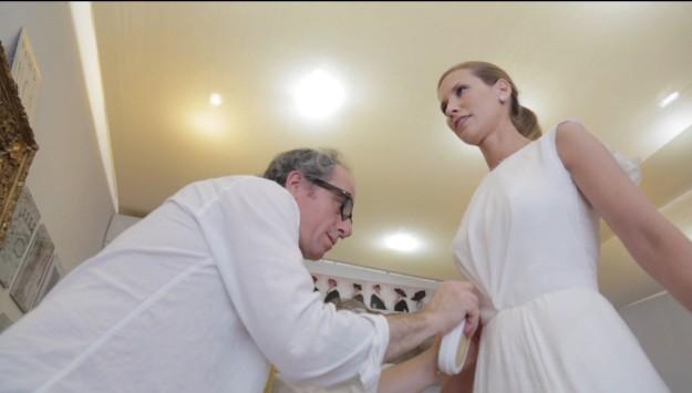 Una chica y un chico mientras ella se prueba el vestido de novia.