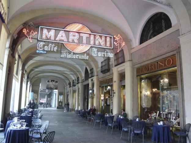 Plaza con mesas y cartel luminoso de Martini.