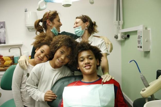 Dos de las odontólogas de la clínica de Barcelona de Dentistas sobre Ruedas, con tres niños al os que atienden