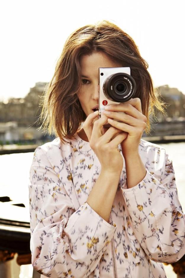 Hanneli Mustaparta, con su inseparable Leica, con mono rosa estampado de flores de Dior.