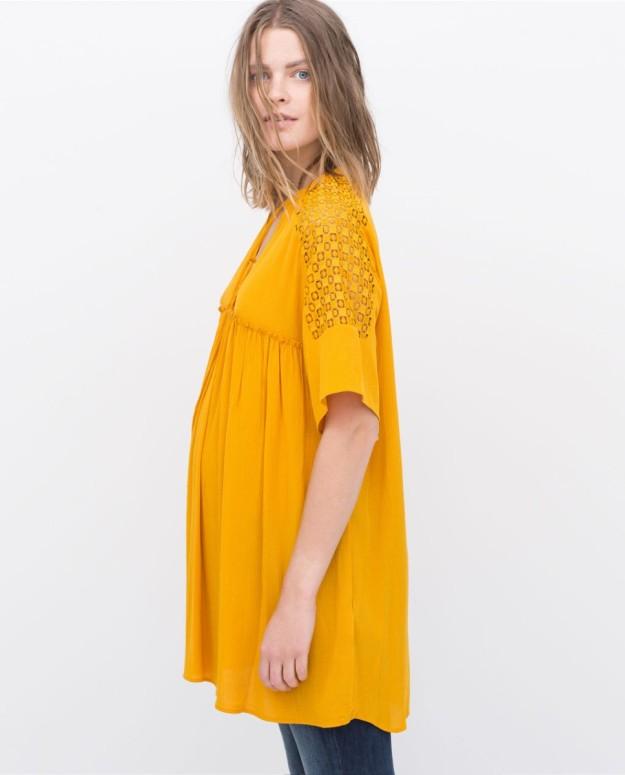 La modelo con vestido-blusón de guipur en color mostaza (29,95 euros).