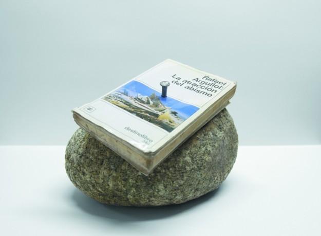Piedra con un libro clavado.