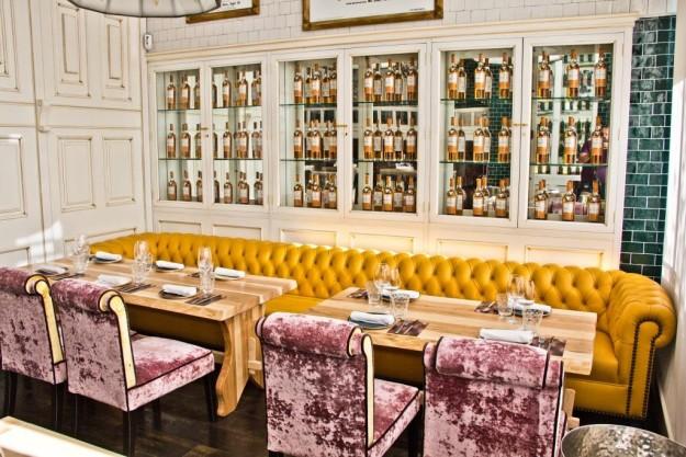 Un chester mostaza y sillas de terciopelo rosa de la sala de La Canica.