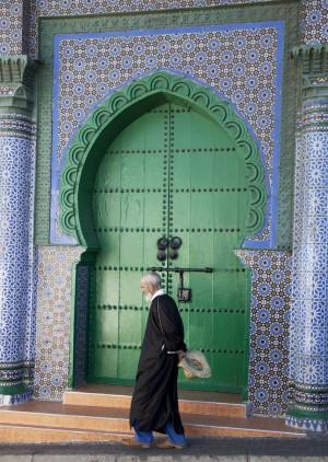 Anciano con kaftán y la puerta de una mezquita.