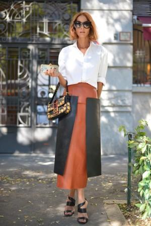 Candela Novembre combina su camisa blanca remangada hasta el codo con una falda midi de piel.