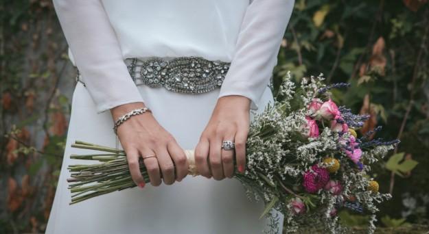 novia con joyas y ramo de flores