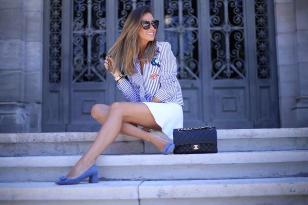 La blogger Marta Carriedo con su look de minifalda blanca y camisa de rayas con parches.