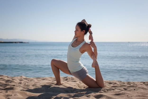 Xuan-Lan realizando yoga en la playa.